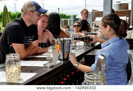 Middletown Rhode Island: Bar tender pouring a bottle of white wine for a young couple to taste at the Newport Winery Vineyard