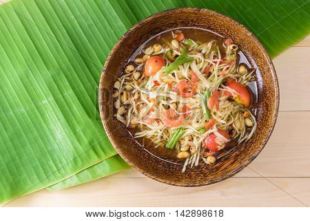 papaya salad (papaya pok pok) top view on a wooden table and green banana leaf Thai local food.