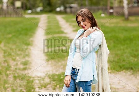 Pensive girl threw a jacket on his shoulder and looked down.Concept Fashion and beauty