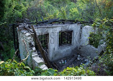 The remains of the burnt house in the woods. Desolation. View from above.