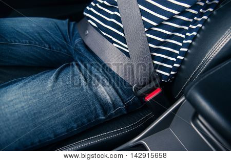 Asian woman fastening seat belt in the carfocus on jeans