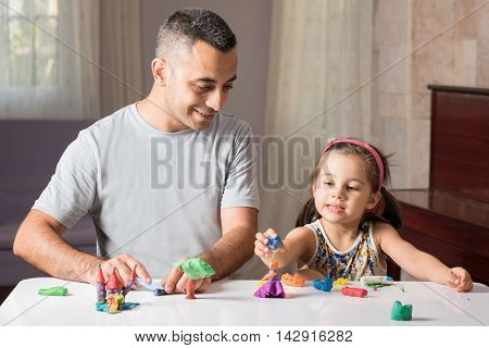 Little Girl Is Playing With Putty Together With Her Father poster