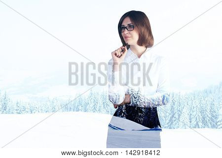 Pondering businesswoman on snowy landscape background with copyspace. Double exposure