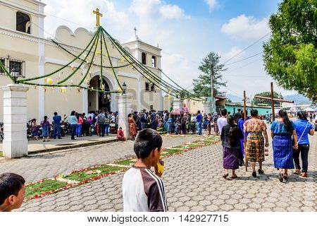 Parramos Guatemala - May 29 2016: Traditionally dressed Mayan women carry crosses for Corpus Christi procession outside church during mass.