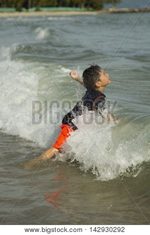 Young asian boy plays with waves in the ocean