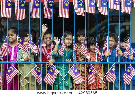 MALACCA MALAYSIA - AUGUST 27 2010: Kids with Malaysia flag 'Jalur Gemilang'.