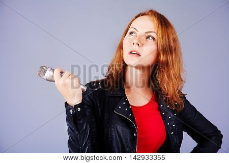 woman is singing rock song with a microphone.  isolated on gray studio background