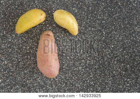Fingerling potatoes on a cutting board in the shape of a face