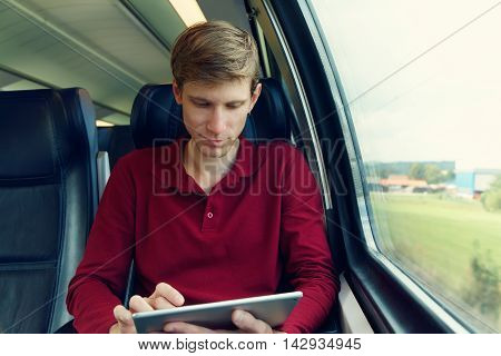 handsome young man using tablet computer on the train. traveler on the road
