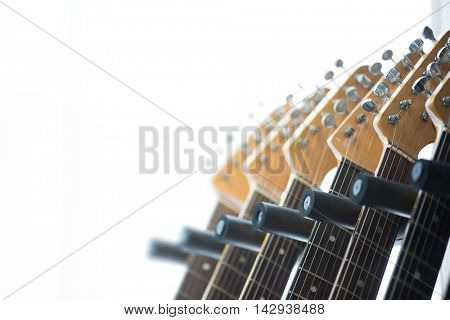 Head section of electric guitars on a guitar rack by a sunlit window. Shallow depth of field. Focus on forehand. Shallow depth of field.