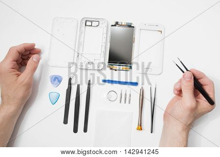 Repairman workplace with phone and special tools. Disassembled smartphone with disassembling instruments and repairer hands on white background. Electronics repair service, device production concept