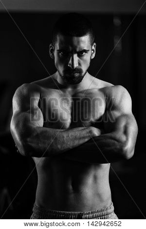 Young Man Standing Strong In The Gym And Flexing Muscles - Muscular Athletic Bodybuilder Fitness Model Posing After Exercises poster
