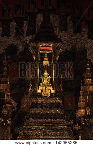 BANGKOK THAILAND - MARCH 28 2016: The Emerald Buddha wears summer season attire made from gold. The Emerald Buddha is the most important buddha image in Thailand at Wat Phra Kaew in Bangkok Thailand.