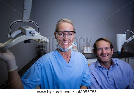 Portrait of smiling dental assistant adjusting light in clinic