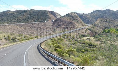 Winding highway through mountainous desert landscape in Arizona, United States of America, two-lane roadway with marking and hard shoulder, blue sky with white clouds,