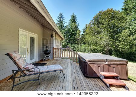 Backyard House Exterior With Patio Area And Hot Tub On The Walkout Deck.