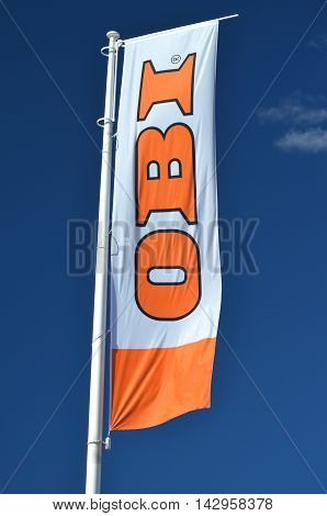 CIRCA AUGUST 2016 - GDANSK: sign of OBI on waving flag against blue sky. OBI is the largest do it yourself retailer in Europe. It was founded in 1970 in Hamburg, Germany.