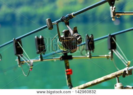 Professional equipment for carp fishing with fishing rods with reel on a support system (rod pod) poster
