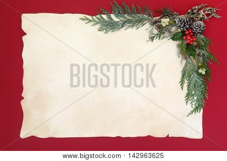 Christmas abstract border with flora of holly, mistletoe, cedar cypress and pine cones on old parchment paper over red background.