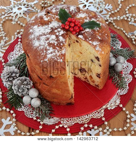 Christmas panettone sweet bread cake with holly berries, silver snowflake and glitter bauble decorations with bead strands over oak table background.