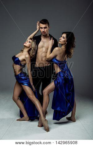 Beautiful young two women dancer in blue top, long blue skirt dancing with man