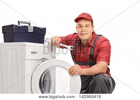Repairman holding a wrench and posing by a washing machine and a toolbox isolated on white background