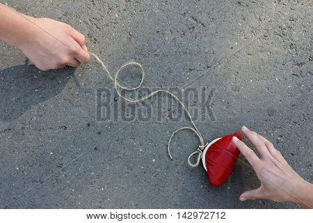 man with a red purse and tied a rope to it entices another person / danger of easy money