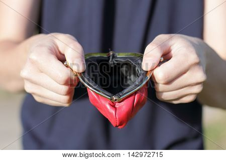 man with open and empty red wallet in the hands / empty purse with no money