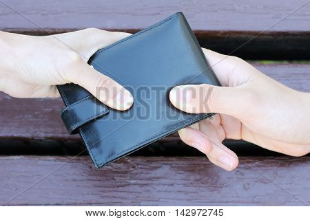 black purse dragging in different directions two human hands / struggle for the purse
