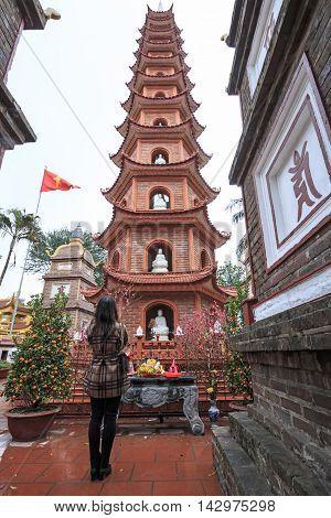 Hanoi, Vietnam - February 23, 2016: Woman Praying In Fron Of The Tran Quoc Pagoda In Hanoi, Vietnam