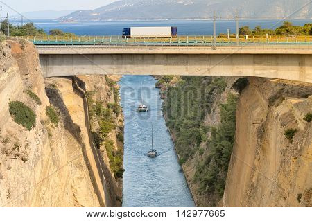 Large truck traversing the bridge of isthmus of Corinth in Greece while the boats are travelling in the bottom.