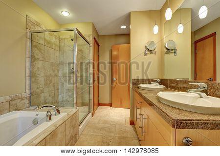Bathroom Interior In Beige Tones With Vanity Cabinet With Granite Counter Top.