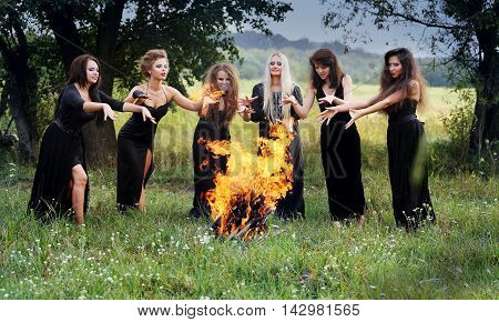 witches conjure near a campfire in the forest