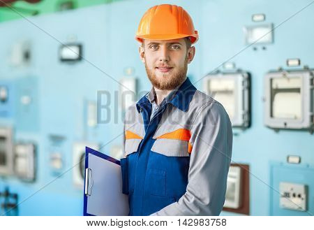 Portrait Of Young Engineer Taking Notes At Control Room
