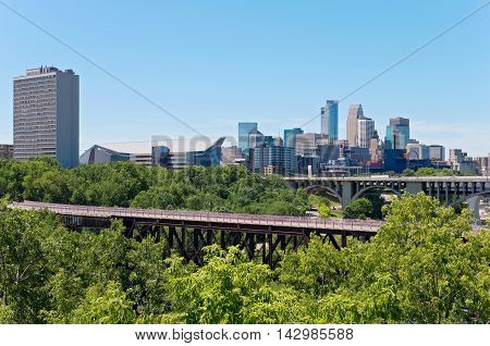MINNEAPOLIS, MINNESOTA/USA - JULY 29, 2016: Minneapolis skyline from East Bank of University of Minnesota and two landmark bridges spanning the Mississippi River.
