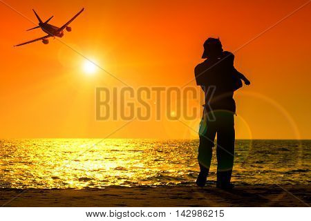 Silhuoette airplane and people on seascape sunset background with sunbeam and lens flare effect