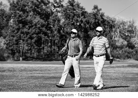 Golfer and caddy on golf course, black and white image