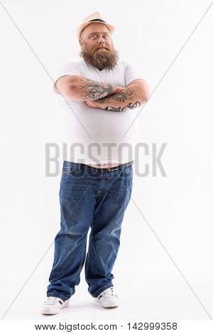 Full length portrait of male fatso standing and looking forward with shock. His arms are crossed and eyes wide open. Isolated on background