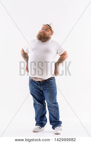 Serious fat man is standing in confident position with arms akimbo. Isolated on background