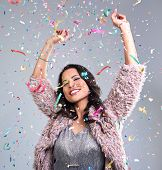 carefree happy woman dancing with arms up at new years eve party falling confetti everywhere poster