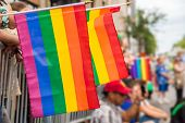 Gay rainbow flags at Montreal gay pride parade with blurred spectators in the background poster