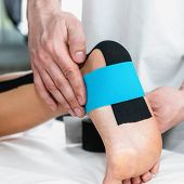Physical therapist placing taping on patient's foot poster