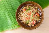 papaya salad (papaya pok pok) top view on a wooden table and green banana leaf Thai local food. poster