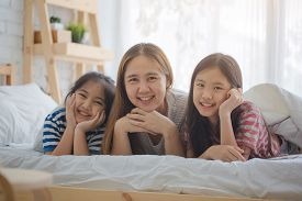 Healthy Asian family smiling and lying on the bed, Happy family