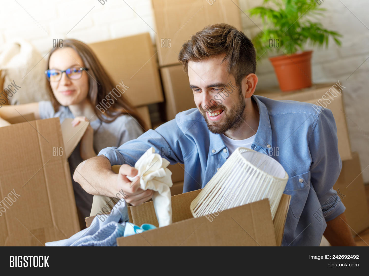 Cheerful Man And Unng Stuff From Carton Boxes In New Apartment Having Fun