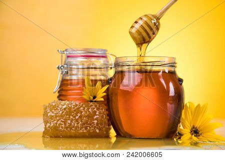 Honey dripping from a wooden honey dipper in a jar
