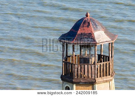 Old Abandoned Wooden Lighthouse. Sea Background. Closeup View