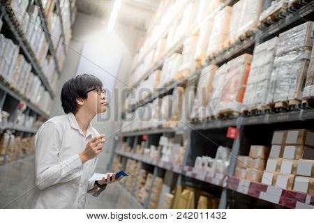 Young Asian Man Checking The Shopping List And Looking For Product In Warehouse Wholesale, Shopping