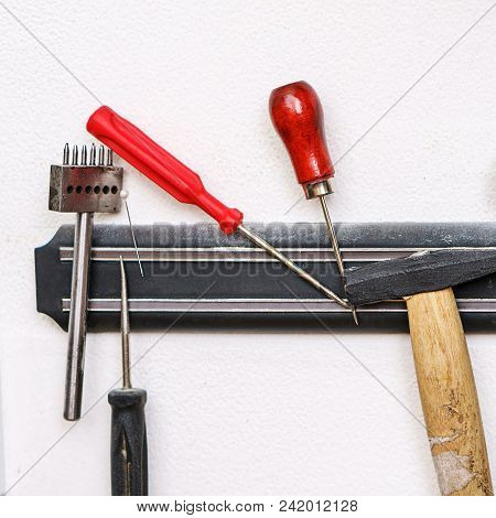 Set Of Tanner Tools Close-up. Awl, Screwdrivers And Hammer Hang On The Magnetic Holder.