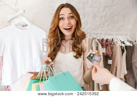 Happy young couple shopping for clothes together at the clothing store, woman holding lots of shopping bags and man giving credit card